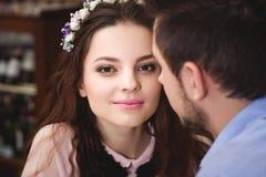 Детеныши влюбились пары сидя на таблице в кафе и идя к стоковое фото