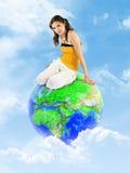 детеныши глобуса девушки земли облаков сидя Стоковое Фото