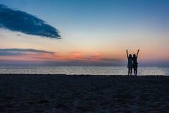Детеныши 2 девушки имея потеху на пляже против фона захода солнца Стоковое Изображение