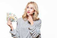 Детеныши думая милая женщина в сером свитере держа пук банкнот евро, смотря вверх с рукой на подбородке, изолированном на белизне стоковые фото