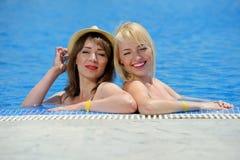 Детеныши 2 девушки в бикини на бассейне Стоковая Фотография RF
