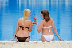 Детеныши 2 девушки в бикини на бассейне Стоковая Фотография