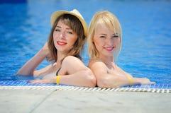 Детеныши 2 девушки в бикини на бассейне Стоковое Изображение RF