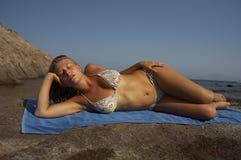 детеныши женщины бикини лежа Стоковая Фотография