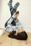 детеныши женщины дома пола лежа Стоковая Фотография
