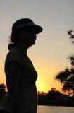 детеныши женщины захода солнца пруда Стоковое Фото