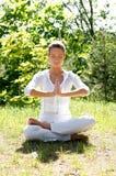 детеныши женщины зеленого цвета травы брюнет meditating Стоковые Фотографии RF