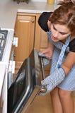 детеныши женщины кухни милые стоковая фотография