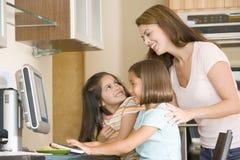 детеныши женщины кухни 2 девушок компьютера Стоковые Изображения RF