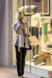 детеныши женщины окна покупкы вечера города Стоковое Изображение