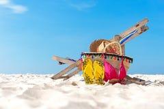 детеныши женщины острова formentera пляжа Бикини и кувырки, шляпа, и сумка около шезлонга на песчаном пляже против голубой предпо Стоковые Фотографии RF