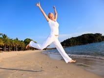 детеныши женщины пляжа счастливые скача Стоковая Фотография