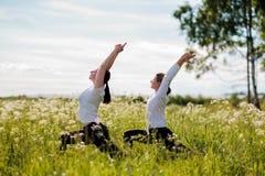 Детеныши 2 женщины практикуя йогу внешнюю в парке Стоковая Фотография RF