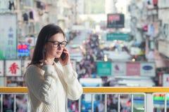 детеныши женщины софы привлекательного передвижного померанцового телефона сидя говоря Стоковая Фотография RF