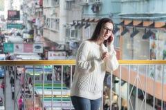 детеныши женщины софы привлекательного передвижного померанцового телефона сидя говоря Стоковое фото RF