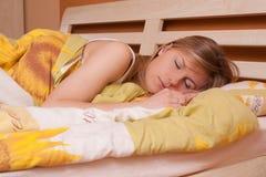 детеныши женщины спать кровати белокурые стоковая фотография