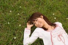 детеныши женщины травы лежа Стоковая Фотография RF