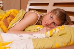 детеныши женщины усмешки белокурых глаз кровати лежа открытые стоковая фотография