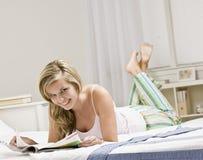 детеныши женщины чтения кассеты кровати Стоковое Изображение RF