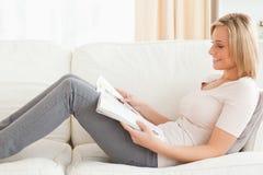 детеныши женщины чтения кассеты стоковое изображение