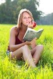 детеныши женщины чтения руки книги яблока сидя Стоковая Фотография