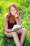 детеныши женщины чтения руки книги яблока сидя Стоковые Изображения