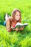 детеныши женщины чтения травы книги лежа Стоковая Фотография