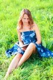 детеныши женщины чтения травы книги сидя Стоковая Фотография