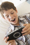 детеныши игры мальчика handheld внутри помещения стоковое изображение