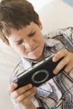 детеныши игры мальчика handheld внутри помещения стоковая фотография rf