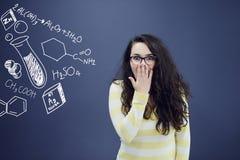 Детеныши изумили женщину на предпосылке голубого серого цвета с диаграммами биологии Стоковые Изображения