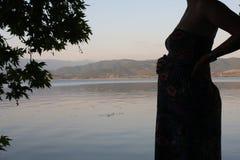 Детеныши и беременная женщина ослабляя рядом с озером Стоковые Фото