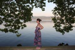 Детеныши и беременная женщина ослабляя рядом с озером Стоковые Фотографии RF