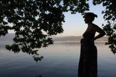 Детеныши и беременная женщина ослабляя рядом с озером Стоковые Изображения