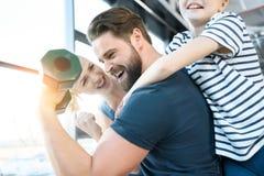 Детеныши и девушка смотря разминку парня с гантелью стоковое изображение