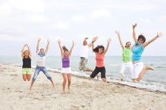 детеныши людей пляжа скача стоковые изображения