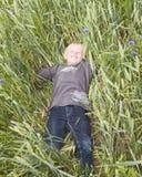 детеныши мальчика лежа Стоковая Фотография