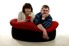детеныши пар кресла счастливые лежа стоковые изображения
