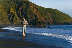 детеныши пляжа побежали человеком, котор Стоковые Изображения