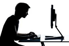 детеныши подростка силуэта девушки компьютера мальчика Стоковое Фото