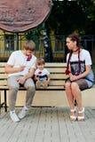 Детеныши поженились пары на стенде в парке, матери с дочерью с леденцом на палочке в руках в одногодичных платьях Стоковые Изображения