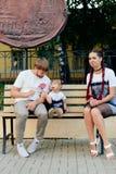 Детеныши поженились пары на стенде в парке, матери с дочерью с леденцом на палочке в руках в одногодичных платьях Стоковое Изображение RF