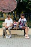 Детеныши поженились пары на стенде в парке, матери с дочерью с леденцом на палочке в руках в одногодичных платьях Стоковые Изображения RF