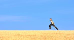 детеныши поля мальчика скача Стоковое Изображение