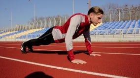 Детеныши подходящий активный красивый человек отжимает нажимают вверх тренировку внешнего спорта, разрабатывая на стадионе на ден видеоматериал