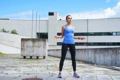 Детеныши, пригонка и sporty женщина скача с прыгая веревочкой Фитнес, спорт, городской jogging и здоровая концепция образа жизни Стоковые Фото