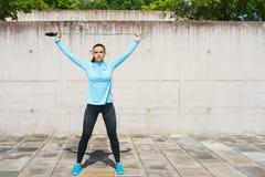 Детеныши, пригонка и sporty женщина скача с прыгая веревочкой Фитнес, спорт, городской jogging и здоровая концепция образа жизни Стоковая Фотография