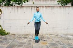 Детеныши, пригонка и sporty женщина скача с прыгая веревочкой Фитнес, спорт, городской jogging и здоровая концепция образа жизни Стоковая Фотография RF