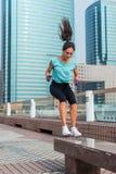 Детеныши приспосабливать скакать активной скачки стенда женщины низкий на улицу города Девушка фитнеса делая тренировки outdoors Стоковая Фотография