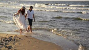 Детеныши соединяют в любов на пляже Красивые пары в белых одеждах Любовники держа руки и обнимать акции видеоматериалы